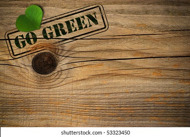 wooden background with green natural heart and go green message