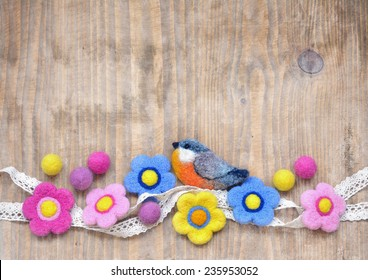 Wooden background with lovely hand felted flowers and bird