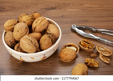 Wooden background with nutcracker and bowl with fresh harvested walnuts