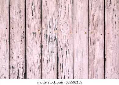 Wooden background. Old shabby  pink colored wooden fence.