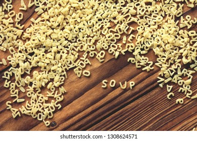 """wooden background with pasta, alphabet, word """" soup"""""""