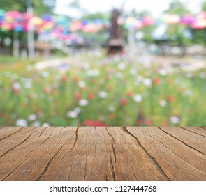 A wooden balcony extends into a colorful flower field. Abstract background and texture of beautiful in natural with blur vission