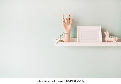 Wooden ball-jointed  hand photo frame and decorating ceramic doll and tillandsia plant on pastel blue wall background