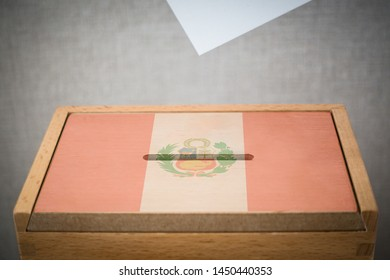 A wooden ballot box and voting paper carved with the flag of Peru