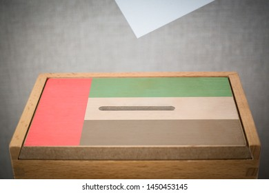 A wooden ballot box and voting paper carved with the flag of United Arab Emirates