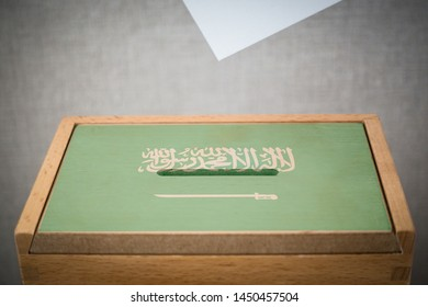 A wooden ballot box and voting paper carved with the flag of Saudi Arabia