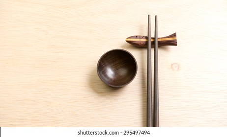 Wooden bamboo chopsticks and bowl for sauce on light wooden surface background. Concept of menu or Asian oriental meal eating culture. Slightly defocused and close-up shot. Copy space.