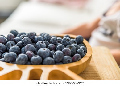 wooden bamboo plate full of fresh blueberries with baby boy on background