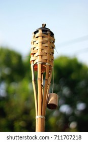 A wooden bamboo tiki torch outside with trees in the background and the sky.