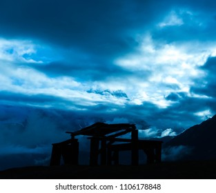 Wooden bank in front of cloudy mountains panorama