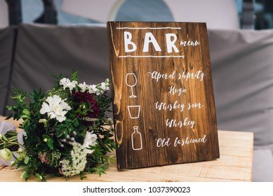 Wooden BAR sign decorative frame stands on the table with composition of flowers on side. Decor. Reception
