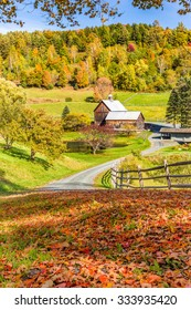 Wooden barn in fall foliage landscape in Vermont countryside.