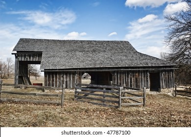 A wooden Barn with a fence in front of it and 3 openings into the barn.