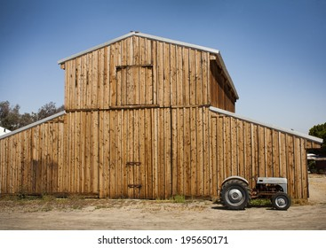 Wooden barn with metal roof with an old tractor to the side.
