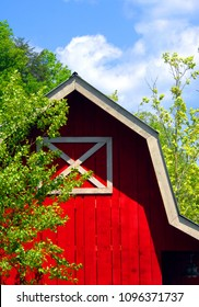 Wooden barn, painted red with white trim, is neat and well maintained.  Blue sky and green trees frame corner of barn.