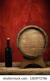 Wooden barrel and black wine bottle on a old oak table of wood.