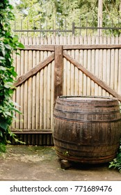 wooden barrel in front of a wooden gate in home yard