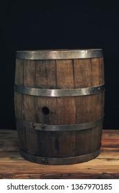 Wooden barrel on a old oak table. Black background behind.