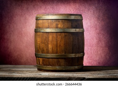 Wooden barrel on a table and pink background
