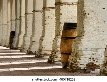 Wooden barrel under a row of brick arches