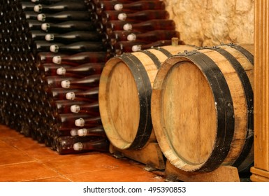 Wooden barrels and bottles with wine  in cellar