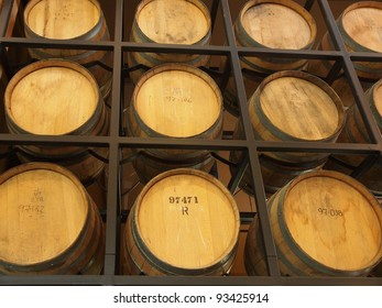 Wooden barrels stacked on the winery shelves