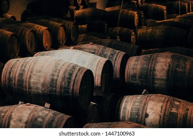 Wooden barrels with wine inside traditional winery with dark cellar for winemaking, Portugal.