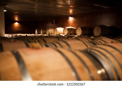 wooden barrels with wine placed in the cellar with dim light
