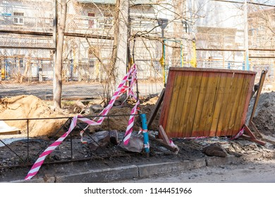 Wooden barricade and the red and white tape protect the construction site. Wooden barricade for construction area. Rose and white tape protects the construction site. Dredged ground