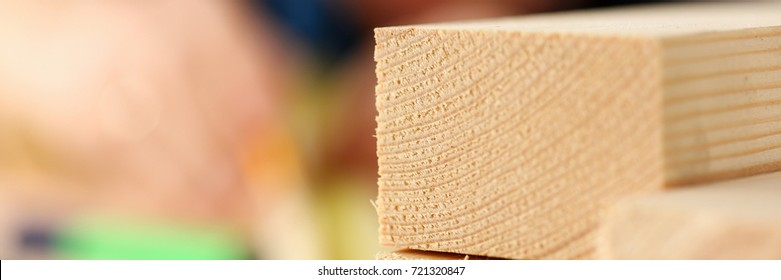 Wooden bars lying in a row closeup with manual worker in background.