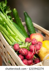 wooden basket, filled with radish, celery, cucumber, pears and apples