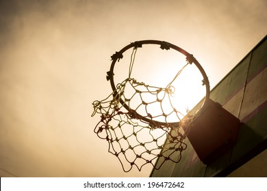 Wooden basketball hoop during sunset.