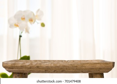 Wooden bathroom table on abstract blurred background with orchid flower
