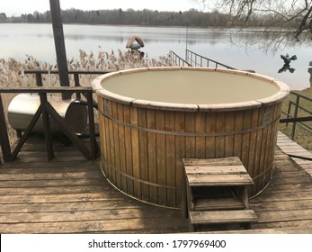 wooden bathtub with a stove on the terrace by the lake in the forest. wooden bath tub