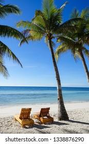 Wooden Beach Chairs on Palm Tree Island, Panglao - Bohol, Philippines