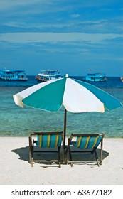 Wooden beach chairs under umbrella.