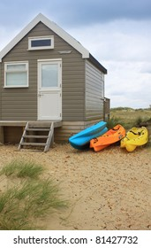 A wooden beach hut or shack with three colorful kayak's to the side of the hut amongst sand dunes and grasses in blue, orange and yellow. Located at Christchurch in Dorset UK.