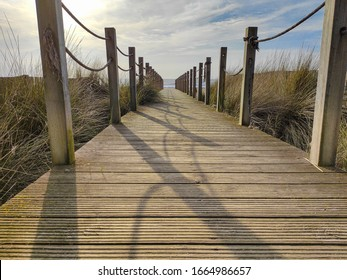 Wooden beach path with rope fence, leading to ocean. Low angle.