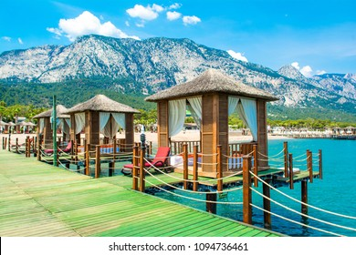 Wooden beach pavilions on the shore of a sandy beach - the Mediterranean coast, Beldibi, Antalya, Turkey
