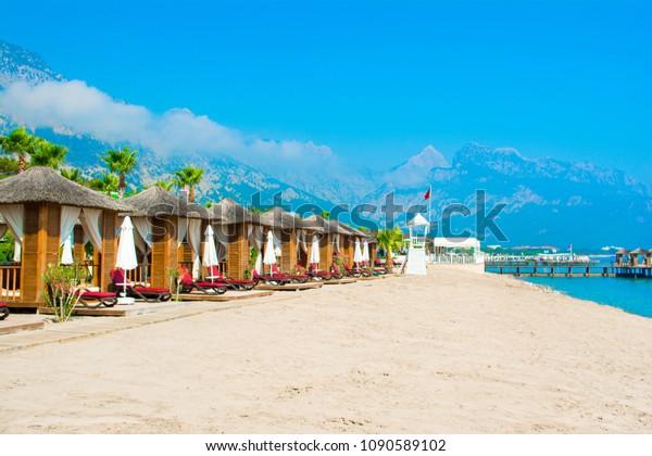 Hölzerne Beach Pavillons am Ufer eines Sandstrandes - Mittelmeerküste, Beldibi, Antalya, Türkei
