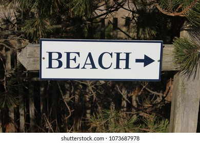 Wooden beach sign with arrow at coastal resort