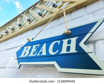 wooden beach sign on white brick wall