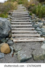 Wooden Beach Stairway. Thick, weathered planks are held together with cable, leading up the sea cliff