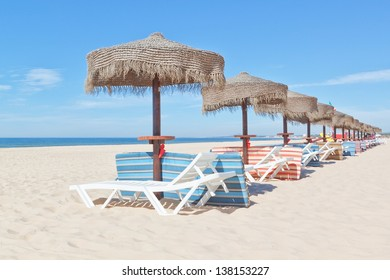 Wooden beach umbrellas and sunbeds on the beach. For the holidays.