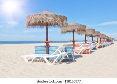 Wooden beach umbrellas and sunbeds on a beach on a sunny day. For the holidays.
