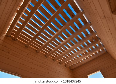 Wooden beams in wooden house on blue sky background on Sunny day. Natural photo.