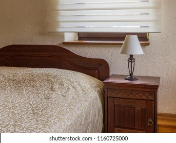 Wooden bed with nightstand and night lamp