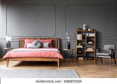 Wooden bed with pink bedding against grey wall with molding in pastel bedroom interior with armchair