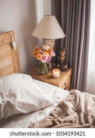 Wooden Bed with White Sheets. A Bedside Table by the Bed with a Lamp, a Bouquet of Flowers from Roses, Candle and Hand Cream