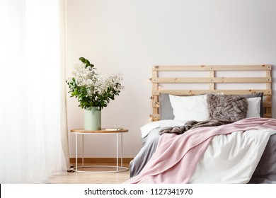 Wooden bedhead with lights by the double bed with fur pillow, grey sheets and pink blanket standing in bright room interior with fresh plants and drapes